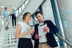 Geschäftsfrau und Mann, die eine Tablette in den Händen halten und an der Kamera lächeln Im Hintergrund sind Gesch?ftsleute lizenzfreies stockfoto