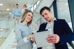 Geschäftsfrau und Mann, die eine Tablette in den Händen halten und an der Kamera lächeln Im Hintergrund sind Gesch?ftsleute stockfoto