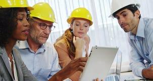 Geschäftsfrau und Mitarbeiter, die über digitaler Tablette sich besprechen stock footage