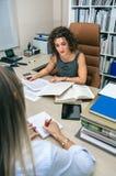 Geschäftsfrau und Sekretär, die mit Dokumenten im Büro arbeiten Lizenzfreie Stockfotografie