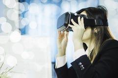 Geschäftsfrau unter Verwendung eines VR-Kopfhörers für Arbeit mit virtueller Realität, mit Spaß und glücklicher neuer Erfahrung,  lizenzfreie stockfotos