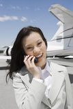 Geschäftsfrau-Using Cellphone With-Flugzeug im Hintergrund stockbilder