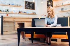 Geschäftsfrau-Using Laptop In-Café Stockbild