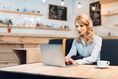 Geschäftsfrau-Using Laptop In-Café Stockfotos