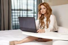 Geschäftsfrau Using Laptop While, das auf Bett liegt Lizenzfreie Stockbilder