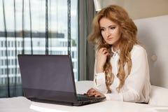 Geschäftsfrau Using Laptop While, das auf Bett liegt Stockbilder