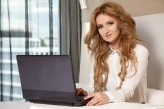 Geschäftsfrau Using Laptop While, das auf Bett liegt Stockfotografie
