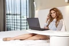 Geschäftsfrau Using Laptop While, das auf Bett liegt Stockbild