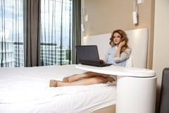 Geschäftsfrau Using Laptop While, das auf Bett liegt Lizenzfreies Stockbild