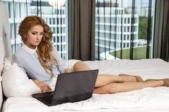 Geschäftsfrau Using Laptop While, das auf Bett liegt Lizenzfreies Stockfoto