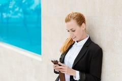 Geschäftsfrau Using Mobile Phone draußen Stockfotografie