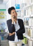 Geschäftsfrau Using Smart Phone in der Apotheke Stockfotos