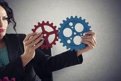 Geschäftsfrau versucht, Gangstücke anzuschließen Konzept der Teamwork, der Partnerschaft und der Integration lizenzfreie stockfotos