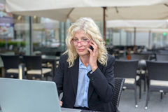 Geschäftsfrau von mittlerem Alter, die auf einem Mobile spricht Stockfotografie