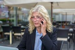 Geschäftsfrau von mittlerem Alter, die auf einem Mobile spricht Stockbild