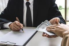 Geschäftsfrau, welche Bestechungsgeld die Form von Dollarscheinen gibt, um Ratgeber zu reifen, während Erfolg das Abkommen zu Fer stockfotografie
