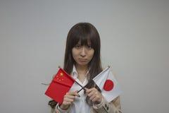 Geschäftsfrau, welche die chinesischen und japanischen Flaggen hält Stockfoto