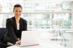 Geschäftsfrau, welche die Laptop-Computer schaut zur Kamera verwendet Stockfotografie