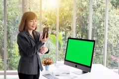 Geschäftsfrau, welche die Ordner sprechen mit Handy vor Computer hält lizenzfreie stockbilder