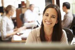 Geschäftsfrau Working At Desk mit Sitzung im Hintergrund Stockfotos