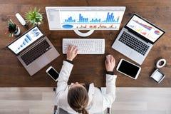 Geschäftsfrau Working With Graphs auf Computer lizenzfreie stockfotos