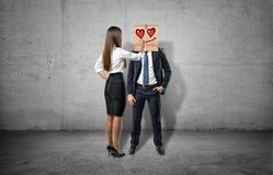 Geschäftsfrau zeichnet ein bezaubertes Gesicht auf dem Kasten, der ein Geschäftsmann ` s Gesicht versteckt Stockfoto