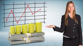 Geschäftsfrau zeigt Hand auf Fässern Gas und Geld Stockbilder