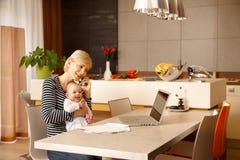 Geschäftsfrau zu Hause mit Baby lizenzfreies stockfoto