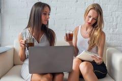 Geschäftsfrau zwei, die auf Sofa mit Laptop-Computer jungen Unternehmensleitern während des Bruches sitzt Stockbilder