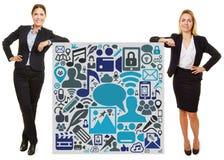 Geschäftsfrau zwei, die auf Zeichen mit Social Media-Ikonen sich lehnt Stockfotografie