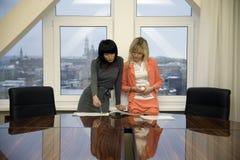 Geschäftsfrau zwei, die in einem Sitzungssaal arbeitet Lizenzfreie Stockfotos