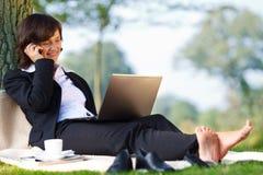 Geschäftsfrauarbeiten im Freien im Park Lizenzfreie Stockfotos