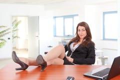 Geschäftsfraubeine auf dem Schreibtisch Lizenzfreie Stockfotografie