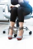 Geschäftsfraubeine, die durch Kette zugeschlossen werden Lizenzfreie Stockfotos