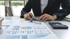 Geschäftsfraubuchhalter, der Finanzdaten bezüglich der Diagrammdokumente, Finanzierung im Arbeitsplatz tuend bearbeitet und berec lizenzfreie stockfotografie