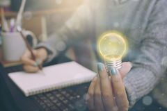 Geschäftsfrauen übergeben das Halten der Glühlampe, Konzept des neuen Ideenesprits Stockbild