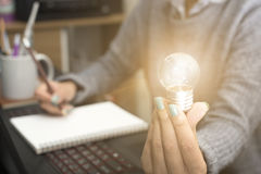 Geschäftsfrauen übergeben das Halten der Glühlampe, Konzept von neuen Ideen Stockfotos