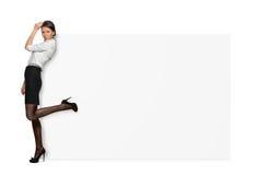 Geschäftsfrauen auf dem weißen Hintergrund, der mit einem Bein zurück angehoben steht und auf einem großen weißen Schild sich leh Lizenzfreie Stockbilder