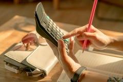 Geschäftsfrauen berechnet die Ausgabe auf dem Holztisch Lizenzfreie Stockfotografie