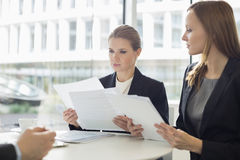 Geschäftsfrauen, die über Dokumenten in der Bürocafeteria sich besprechen Stockbild