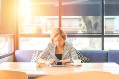 Geschäftsfrauen, die auf Sofa und Gebrauchstablette sitzen Frauen, die nahe dem Fenster in der Kaffeestube sitzen lizenzfreie stockfotografie
