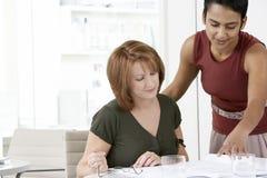 Geschäftsfrauen, die Dokumente am Schreibtisch lesen Stockfotografie