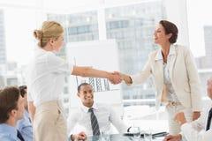 Geschäftsfrauen, die ein Abkommen bei einer Sitzung machen Stockbild