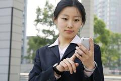 Geschäftsfrauen, die einen Handy anhalten stockfotografie
