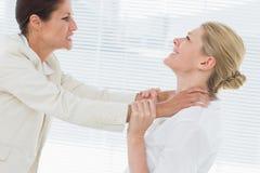 Geschäftsfrauen, die einen heftigen Kampf im Büro haben Stockbild