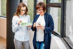 Geschäftsfrauen, die einen Snack im Büro essen lizenzfreie stockfotos