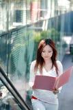 Geschäftsfrauen, die Faltblatt auf Rolltreppe anhalten Stockbilder