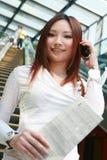 Geschäftsfrauen, die Faltblatt und Welle auf Rolltreppe anhalten Stockbilder