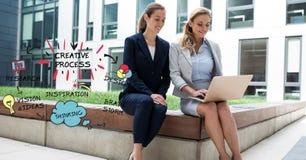 Geschäftsfrauen, die Laptop beim Sitzen auf Stützmauer durch kreative Prozessgraphiken verwenden stockfoto