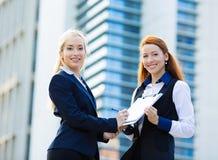 Geschäftsfrauen, die Lastenheft unterzeichnen Stockbilder